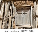 Wooden cross on window of mud church - stock photo