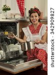 Small photo of Retro styled housewife loads the dishes in the dishwasher. 1950s style post processing emulation.