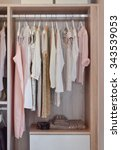 Small photo of modern closet with row of dresses hanging in wooden wardrobe