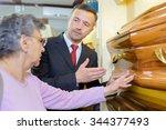 undertaker showing a woman a... | Shutterstock . vector #344377493