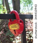 "Small photo of Love padlock (""Let it be a strong family"") affixed to a fence in park"