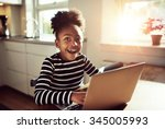 Small photo of Black girl sitting playing on a laptop computer at home looking at the camera with a joyful expression of amazement and wonder