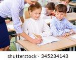 lesson at school. teacher leans ...   Shutterstock . vector #345234143