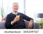 Portrait Of Senior Man Holding...