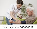 young nurse taking old man's... | Shutterstock . vector #345680597