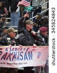 Small photo of NEW YORK - NOV 25 2015: A boy waves the American Flag while on the shoulders of a vet behind the Airborne Rakkasan 187th Infantry Regiment Combat Team banner at the Americas Parade on Veterans Day.