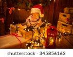 Cute Child In Santa Hat Sittin...