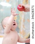cute baby boy  try to touch  red apple - stock photo