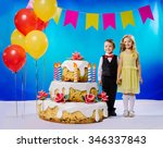 Small photo of a little girl and a little boy holding hands near a big birthday cake with candles and colorful balloons on a blue background
