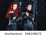 Small photo of Women dressed in latex and leather dominate the game play. A woman in a dark room in the cell the prisoner.