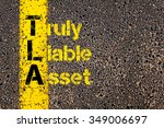 Small photo of Concept image of Accounting Business Acronym TLA Truly Liable Asset written over road marking yellow paint line.