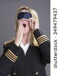 Small photo of Sleepy aircrew officer yawning and using an eye shade