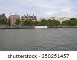 Small photo of View of Victoria Embankment in London, England across Thames river with boats and buildings of original New Scotland Yard, now called the Norman Shaw Buildings