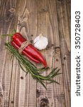 Small photo of Set of cuisine natural organic eco products ingredient for tasty piquant dish with piquant savour allspice tied by rope red raw chili peppers ripe aromatic garlic studio on wooden background, vertical