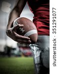 Small photo of Cropped image of sportsman holding American football against pitch