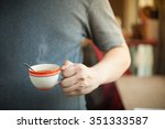 Small photo of The man wearing grey t-shirt holding coffee cup in his left hand in afternoon time