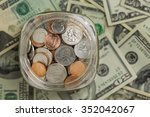 Small photo of Looking down on glass jar filled with coins on a background of paper money. Small savings add up.