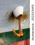 Small photo of anchor on a chain hanging from the ship fairlead