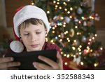 Young Boy Wearing Santa Hat An...