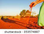 Small photo of pouring sand in the wind sunset at red sand dune on Lasseter Highway near - Kata Tjuta National Park in Central Australia
