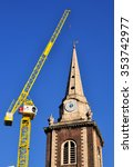 Small photo of LONDON - NOVEMBER 22, 2015. The tower of St Botolph's church built in 1744 with a yellow construction crane redeveloping the surrounding land at Aldgate, London, UK.