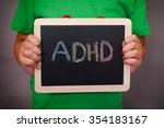 Small photo of Young boy holds ADHD text written on blackboard. ADHD is Attention deficit hyperactivity disorder. Close up.