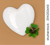 Small photo of White porcelain heart and four leaf clover on brown corrugated paper; All the best for New Year; Good luck; Happy Valentine's Day