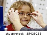 girl trying on eye glasses - stock photo