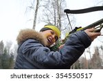 Small photo of Boy with yellow paint on the face of aim with arbalest in forest