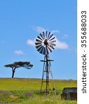 Small photo of Landscape with windmill water pump on a farm swart land South Africa