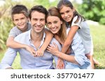 parents giving piggyback ride... | Shutterstock . vector #357701477