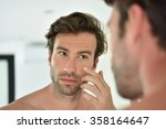 Handsome Man Applying Facial...