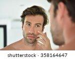 Handsome Man Applying Facial...