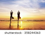 Two People Practicing Yoga Tre...