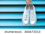 hand holding pair of shoes. | Shutterstock . vector #360673313