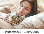 Girl Lying In Bed With Her Cat