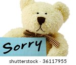 "Front view of teddy bear toy with ""Sorry"" note, isolated on white background - stock photo"
