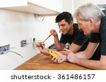 Small photo of Electrician With Apprentice Working In New Home