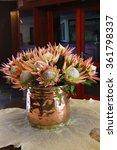 Copper Vase Of Orange Proteas