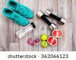 Small photo of Fitness equipment. Healthy food. Sneakers, water,apple on wooden background