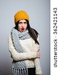 Small photo of Eastern brunette girl looks with distaste, hipster in winter clothes, a photo studio, portrait emotions