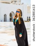 Small photo of Woman dreaming at the grand mosque of Sheikh Zayed Mosque in Abu Dhabi wearing abaya, paranja. Travelling.
