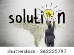 Small photo of Young businessman painting a bright yellow bulb with a brush in the word 'solution' instead of the second 'o' on the white wall. Dollar tornado under it. Back view. Concept of finding a solution.