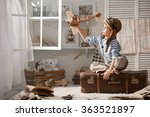 little boy sits on a suitcase... | Shutterstock . vector #363521897