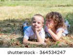 Small photo of Amicable and little, beautiful and happy girl and the boy lie on a fresh grass during a summer time dreaming of love