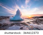 Eruption of Strokkur geyser in Iceland. Winter cold colors, sun lighting through the steam