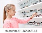 Little Girl Choosing Glasses A...