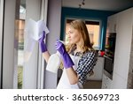 a young woman cleans the window.... | Shutterstock . vector #365069723