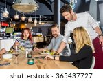 young waiter serving food to... | Shutterstock . vector #365437727