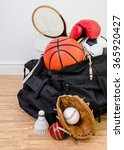 Small photo of sports equipment in a holdall sports bag on a gym floor. football, baseball, cricket, basketball, boxing, badminton, squash. Portrait with copy space.